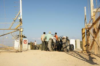 Des soldats israéliens vérifient les permis des fermiers qui veulent travailler sur leurs terres à Jayyous (photo W. Parry)
