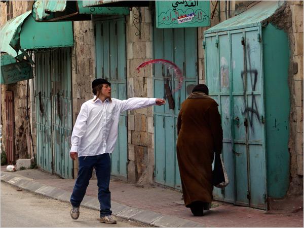 Un colon jette du vin sur une femme palestinienne