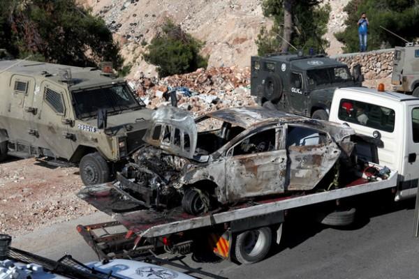 Des soldats israéliens sécurisent la zone autour d'une voiture carbonisée près d'Hébron, en Cisjordanie, le 13 juin, après que trois adolescents israéliens furent portés disparus la veille. (Mamoun Wazwaz/APA Images)