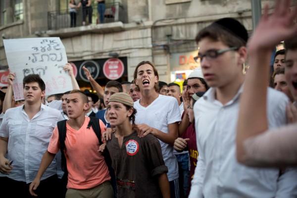 Lors d'une manifestation de la droite à Jérusalem, une pancarte proclame « Que Dieu venge leur sang » et un jeune porte un autocollant déclarant « Kahane avait raison », en référence au dirigeant du mouvement violent des colons, originaire de Brooklyn. 1er juillet 2014. (Tali Mayer/ActiveStills)