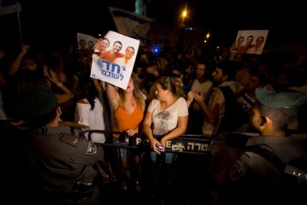 Des manifestants de droite crient des slogans anti-palestiniens lors d'un rassemblement devant la résidence du Premier ministre israélien à Jérusalem, le 5 juillet. Les manifestants lèvent des affiches montrant les trois adolescents assassinés avec le texte, «Unis pour les ramener chez eux». (Faiz Abu Rmeleh/ActiveStills)