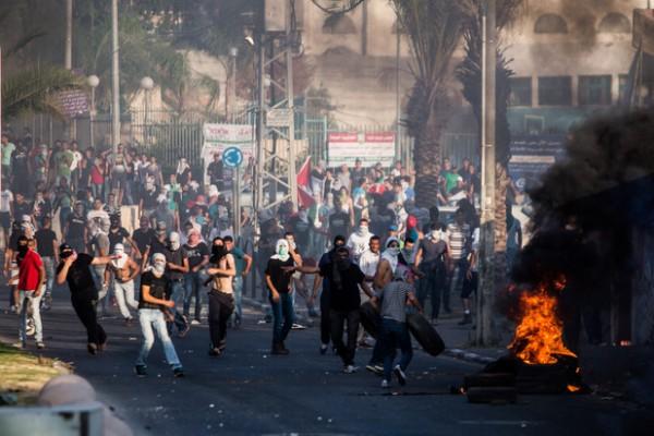 Des manifestants dans la ville palestinienne d'Arara dans le nord de ce qui est actuellement Israël lancent des pierres sur la police israélienne lors d'une manifestation après l'assassinat de Muhammad Abu Khudair, le 5 juillet. (Yotam Ronen/ActiveStills).